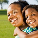 happy african american mother and daughter piggyback outdoors