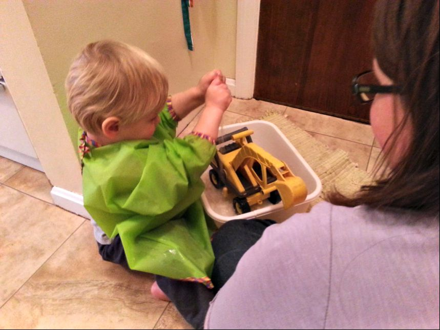 "In this picture my son wanted to play with one of his construction vehicles. We remembered that it was outside and muddy, so instead of saying ""no"" we said ""yes"" then gave him an apron to wear, a basin, a sponge, and a large towel. He spent 25 minutes washing his truck, completely immersed in the activity. True, he truck was clean-ish, but it wasn't just about having a clean truck. It was about respecting his interests and needs and giving him the space and material to complete his work."